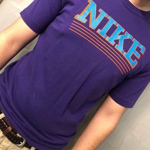 Purple shirt with blue Nike logo.